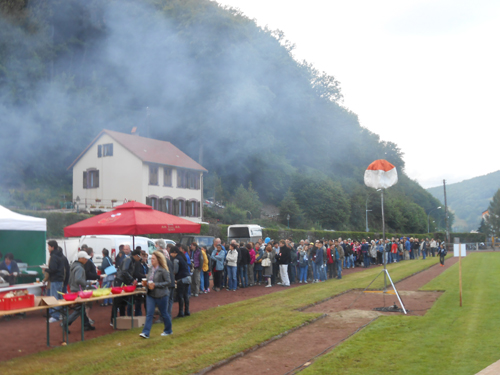 The queue for the BBQ along one side of the playing field.