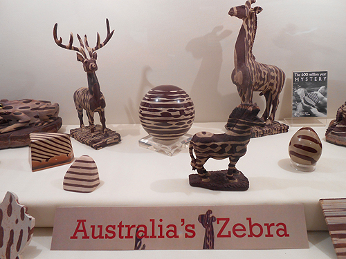 "Australia's ""Zebra Stone"" is a compact siliceous claystone. This display of carved ornaments and figures was compiled by the University of Wollongong. All the specimens are from the Marty Zinn collection."
