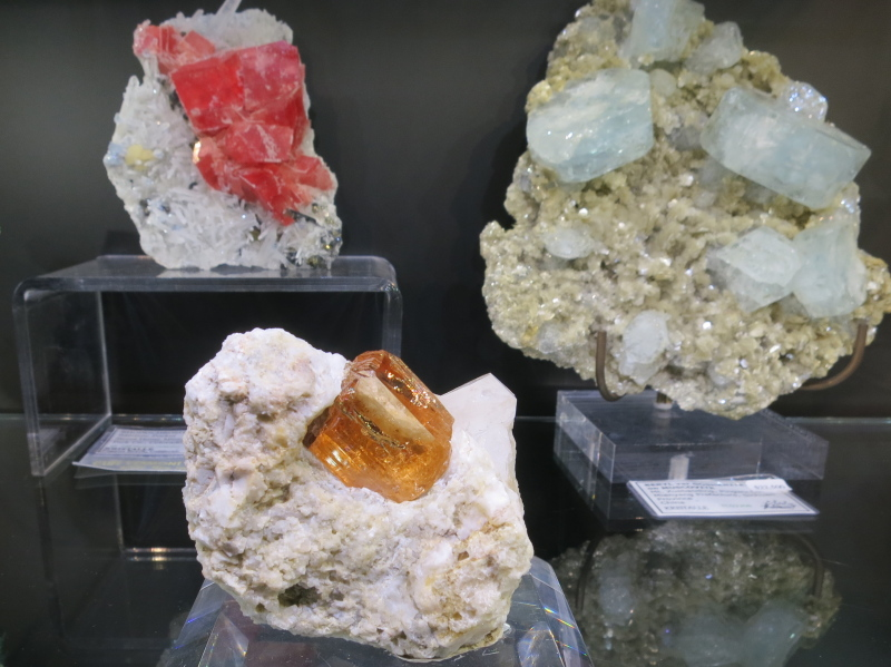 An amazing Topaz from Katlang, Pakistan with approx 2.5cm crystal, accompanied by a Sweet Home Rhodochrosite on the rear left, and Goshenite specimen from China on rear right