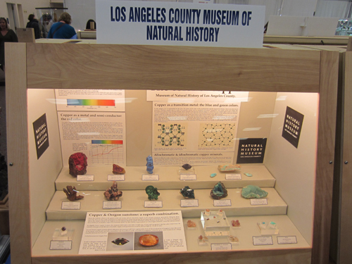 The display from the Los Angeles County Museum of Natural History, with a beautiful Chalcotrichite from the Czar Mine, Bisbee, Cochise County, Arizona USA in the far left corner.